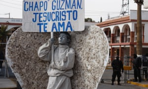 A member of an evangelical church dressed as angel holds a sign which reads, Chapo Guzman, Jesus Christ loves you during a demonstration against violence in the city of Ciudad Juarez.