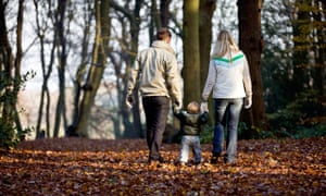 A young couple walking with their son in the park