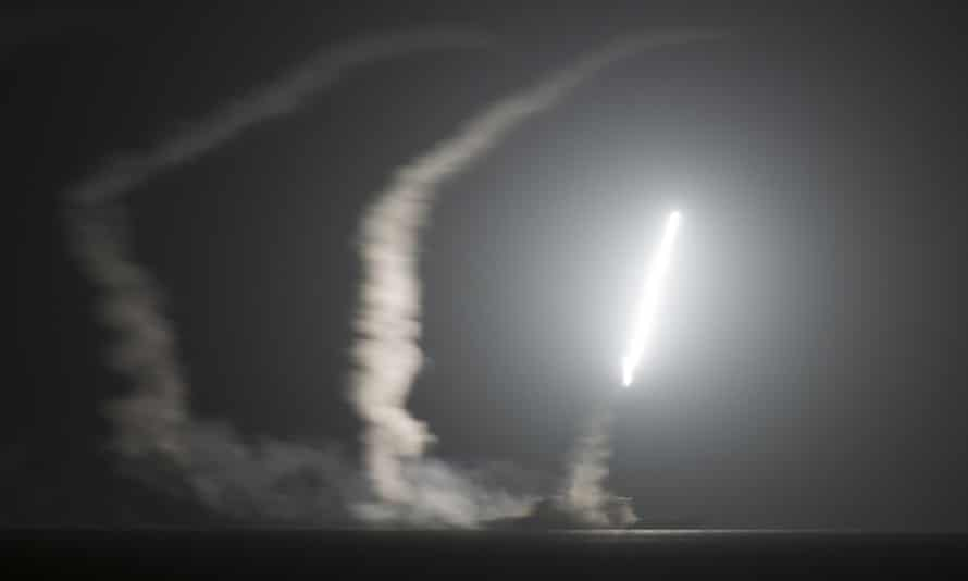 As seen from the aircraft carrier USS George HW Bush, the guided-missile cruiser USS Philippine Sea launches a Tomahawk cruise missile in the Arabian Gulf against Isis.
