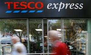Pedestrians pass a Tesco Express shop in London