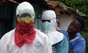 Medical workers of the John Fitzgerald Kennedy hospital in Monrovia put on protective suits prior to carrying bodies of Ebola virus victims