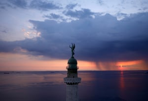 Trieste, Italy: The Vittoria Light, overlooking the Gulf of Trieste at sunset as a storm approaches.