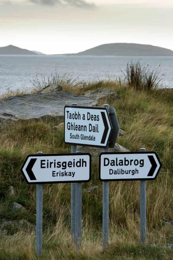 Gaelic language signs point the way at Ludag, South Uist, looking over the Sound of Eriskay