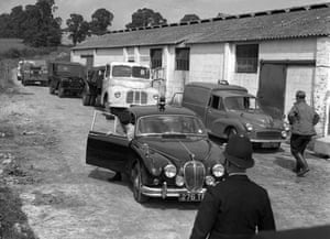 A police-car escorts the lorry and two Land Rovers, which police believe the bandits carried much or all of their haul after the  2.6 million pound mail train robbery, out of Leatherslade Farm, Oakley, Bukinghamshire, where the gang hid after the crime.