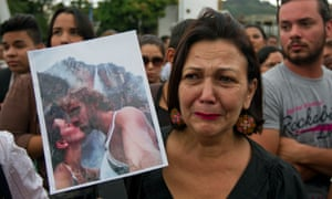 A woman holds up a picture of former Miss Venezuela Monica Spear and her ex-husband Thomas Berry