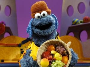 cooking monster from sesame street holding fruit basket