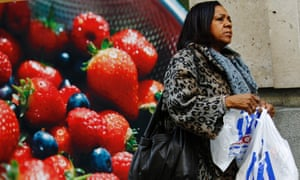 A woman carries a Tesco shopping bag outside a branch of the supermarket in London