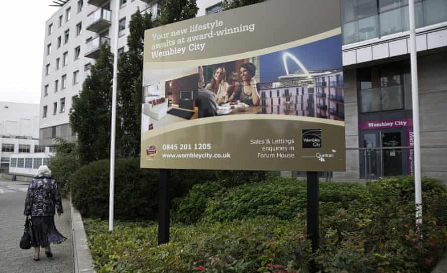 A pedestrian passes a marketing sign outside the Wembley City retail and residential complex in north-west London.