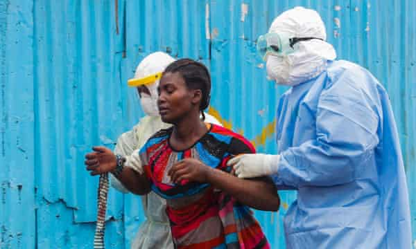Liberian nurses escort a suspected Ebola patient into a treatment center in Monrovia