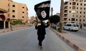 An Islamic State memberwaves an Isis flag in Raqqa