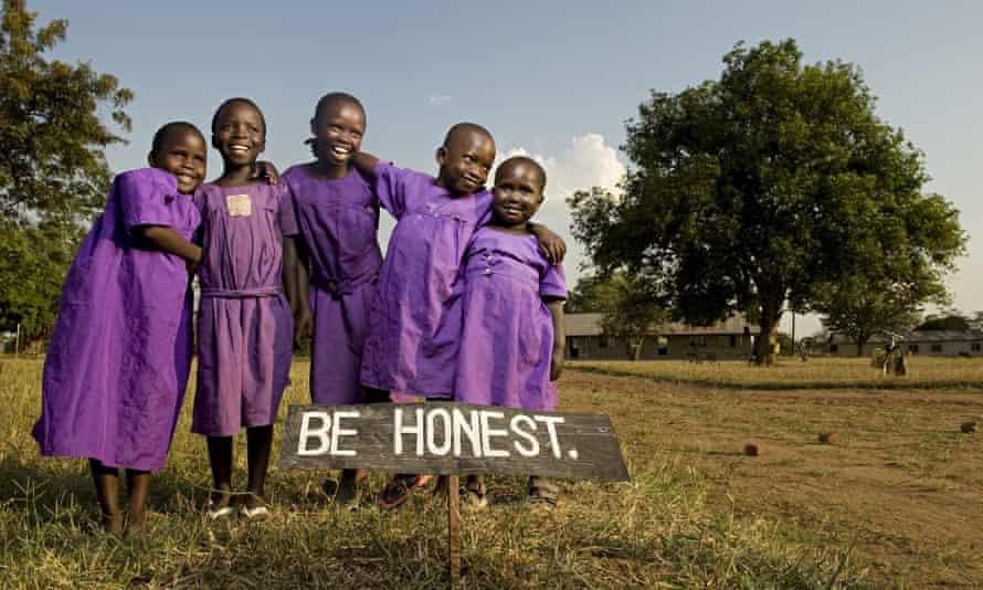 Tiriri primary school pupils by a sign reading Be Honest, Katine, Uganda