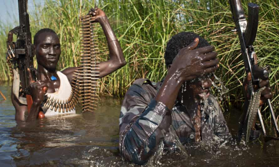 Rebel soldiers patrol and protect civilians from the Nuer ethnic group as they walk through flooded areas in the town of Bentiu, South Sudan in September.