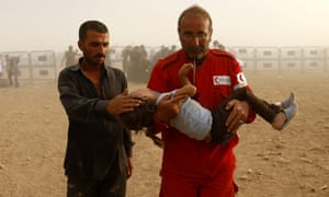 Syrian refugees are helped by a Red Crescent worker as they cross the Syrian-Turkish border near Sanliurfa, Turkey, 25 September 2014. In recent days, Turkey has seen the 'biggest influx' of Syrian refugees since the start of the war three years ago, said the UN agency for refugees (UNHCR).