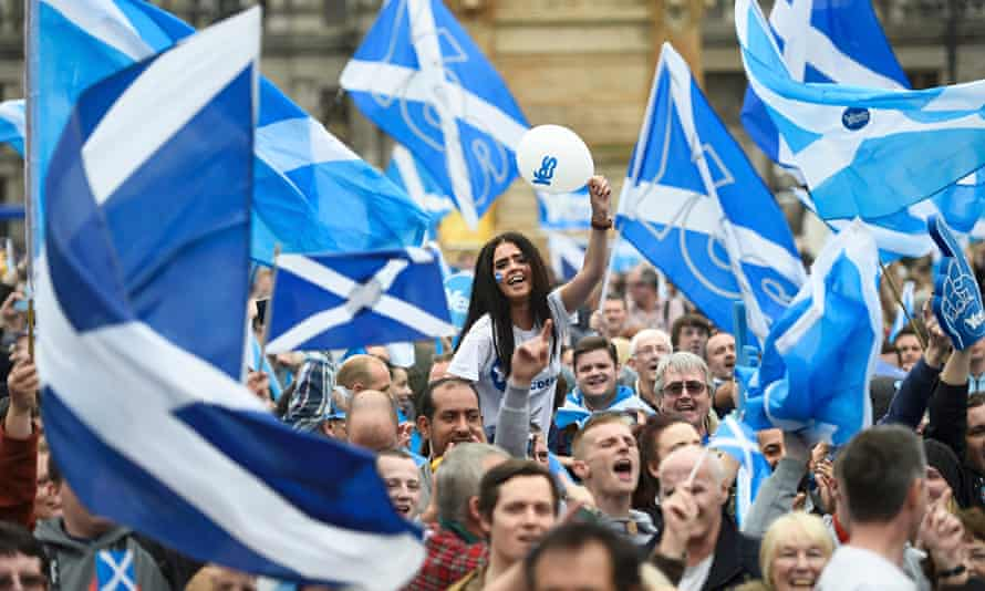 Campaigners wave Scottish Saltires at a yes campaign rally in Glasgow