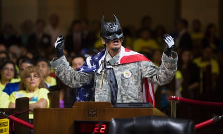 A person wearing a Batman mask speaks prior to a city council vote to increase minimum wage in Los Angeles.