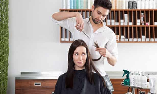 A woman having her hair cut in a salon by a man with a beard.