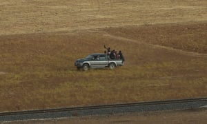 Turkish Kurds load a pick-up after they cross the border to join Syrian Kurdish fighters in Kobani