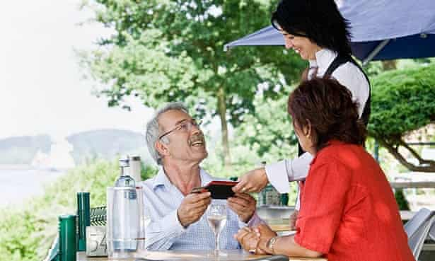 Waitress bringing the bill to the table at an outdoor terrace restaurant