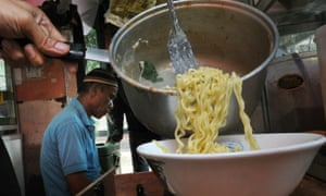 A vendor prepares instant noodles produced by the 'Indofood' food company at a stall in Jakarta on October 12, 2010