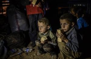 Syrian Kurdish children sit and wait after crossing the border near Suruç