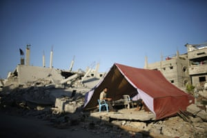 Palestinians sit in a tent erected upon the ruins of their house, which witnesses said was destroyed during the seven-week Israeli offensive in the east of Gaza City