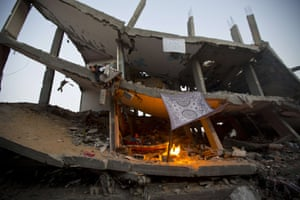 A Palestinian boy sits inside the ruins of his family house which was destroyed during the 50-day conflict between Israel and Hamas