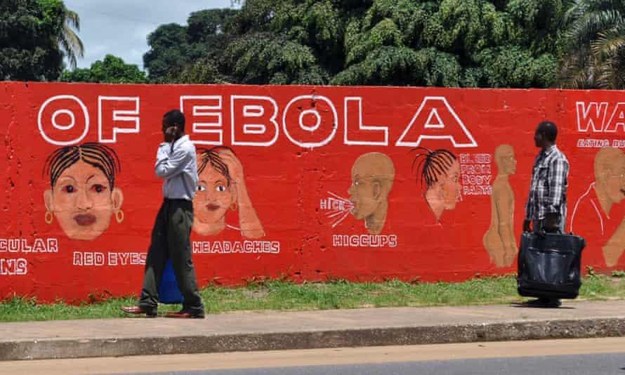 Pedestrians walk past a mural showing the symptoms of the Ebola virus in Monrovia, Liberia, September 26, 2014. REUTERS/James Giahyue (LIBERIA - Tags: POLITICS HEALTH):rel:d:bm:GF2EA9Q1B5401