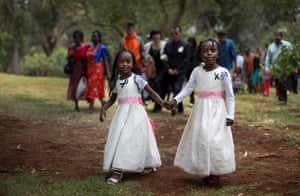 Gloria, left, whose father Christopher Chewa was killed in the Westgate Mall attack, walks with her cousin Miriam and other families of the victims to lay flowers at the Amani Garden memorial site in Nairobi. Kenya is marking the first anniversary of the attacks at the Westgate mall