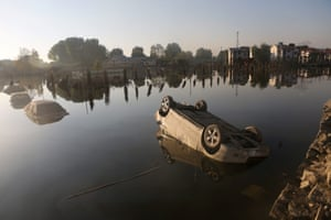 Vehicles are half-submerged in floodwaters in Rajbagh, Indian Kashmir. At least 300 people have died in the worst-ever floods witnessed in a century