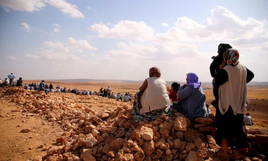 Turkish Kurds gather to see the fighting between Isis fighters and the Protection of the Kurdish people (YPG) fighters in the next village on the Syrian side.