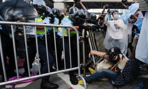 A protester clings to a barrier fence clashes with riot police