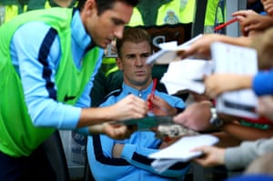 Joe Hart of Manchester City looks on from the bench as team-mate Frank Lampard signs autographs.