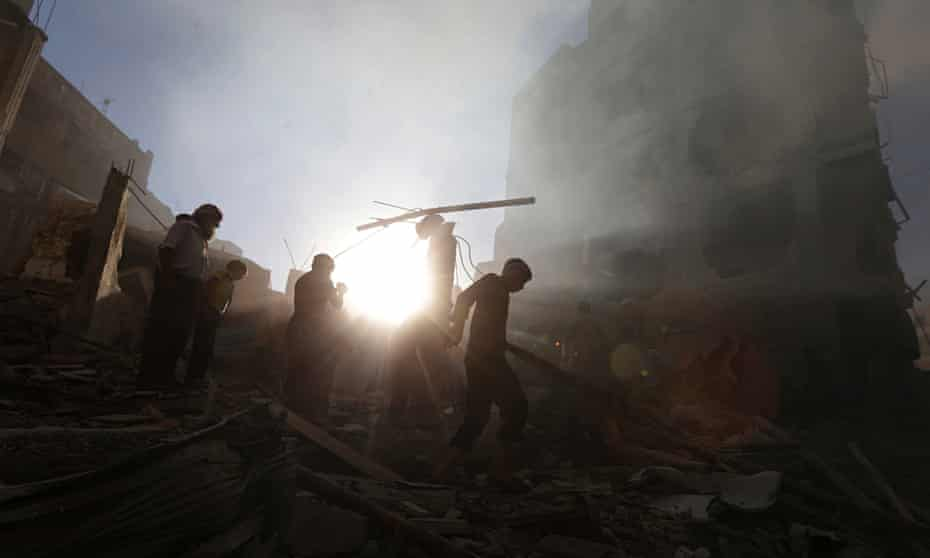 Residents in Douma, near Damascus, survey the aftermath of an airstrike