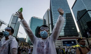 A pro-democracy demonstrator wearing a mask and goggles to protect against pepper spray and tear gas gestures during a rally near the Hong Kong government headquarters.