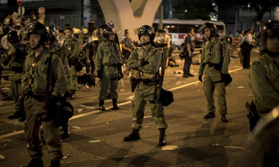 Police officers hold their ground surrounded by pro-democracy protesters on a major road in the heart of Hong Kong.