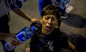 A pro-democracy demonstrator pours water over a man's face after police fired teargas at protesters in Hong Kong.
