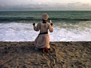 Holding ceremonial candles in her right hand Barbara Jolola, a Nigerian evangelical Christian woman,  prays while facing the sea on Bar Beach, in Lagos, Nigeria, March 9, 1999.