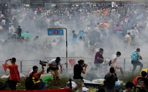 People disperse after police fired tear gas upon pro-democracy demonstrators near the Hong Kong government headquarters.