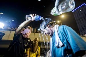 Protesters pour water over the head of a fellow demonstrator during riots that followed a pro-democracy protest in Hong Kong.