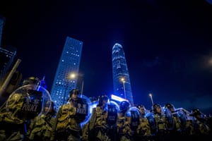 Police officers stand in front of pro-democracy protesters during a demonstration in Hong Kong.