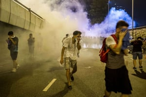 Protesters protect themselves from tear gas fired by police during riots that followed a pro-democracy protest in Hong Kong.