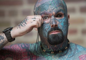 A man who has changed his name to King of Ink Land King Body Art The Extreme Ink-ite  adjusts his monocle as he poses during the 10th International Tattoo Convention in London