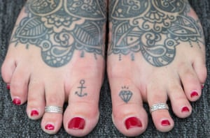 A woman shows her tattooed feet during the 10th International Tattoo Convention in London