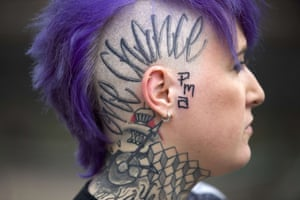 A woman displays a tattoo on the side of her head and neck at the London Tattoo Convention in London