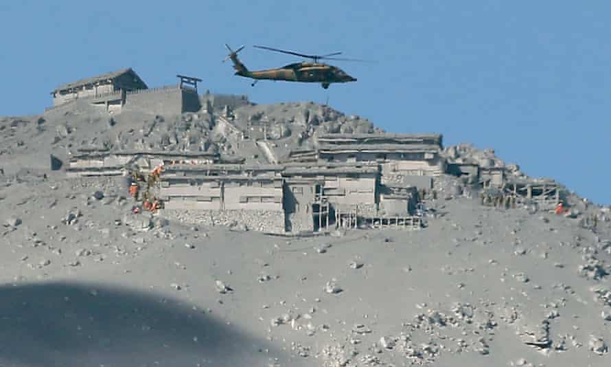 A rescue helicopter searches for survivors at the mountain shrine at the ash-covered summit of Mount Ontake.
