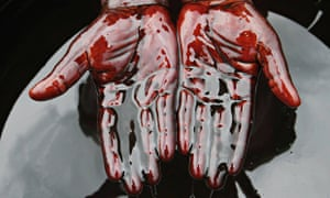 A man covers his hands in crude oil during a protest against Shell