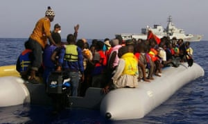 Migrants, many of them already in life jackets, onboard a long dinghy-style vessels after being rescued by the Italian Navy 22 September 2014