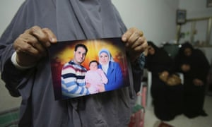 Mother of Palestinian Shukri al-Assouli, holds his photograph in Gaza. He set off from Alexandria on September 6 with his wife and two children on a ship with 400 migrants on board that was destined for Italy, but the vessel sank and he was rescued by a Japanese commercial ship and taken to Greece