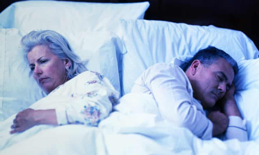 In a bed a worried older woman awake and a sleeping older man