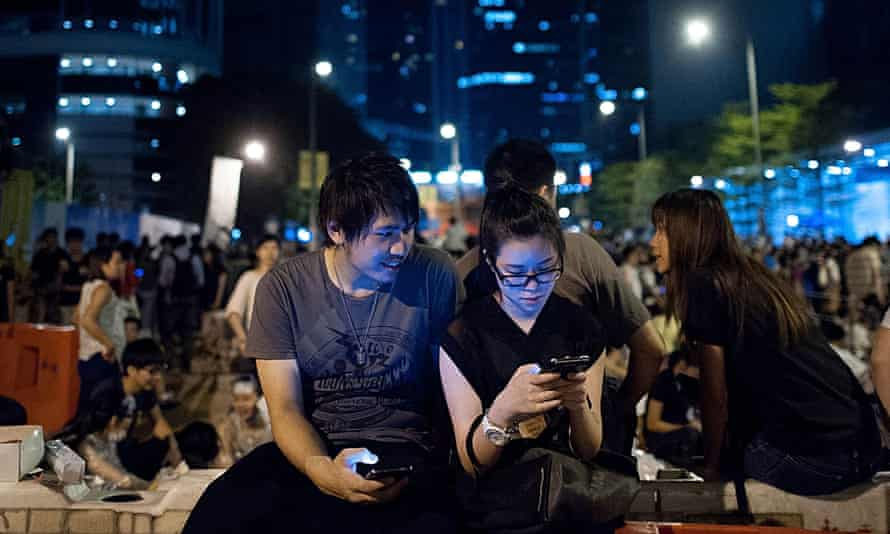 Pro-democracy supporters looking at a phone